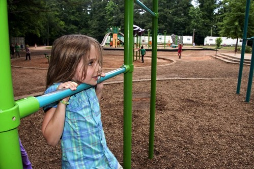 Face of girl hanging by her arms from one of the playground green and blue pull up bars 725x482