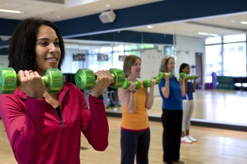 Happy girl using light weight dumbbells on fitness 725x482