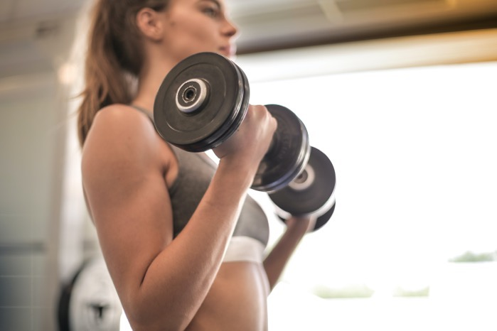 Woman in gray sports bra holding black dumbbell 3757376